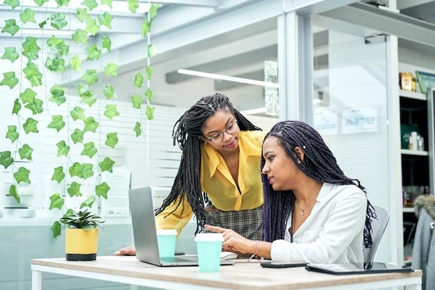 Dois colegas de trabalho afro-americanos sorridentes no escritório trabalhando juntos
