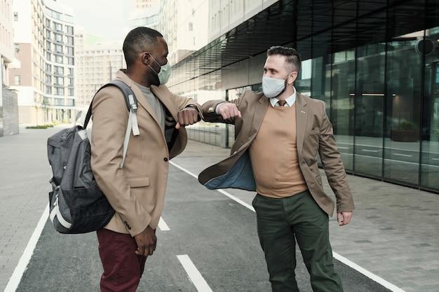 Dois colegas de trabalho com máscaras protetoras se cumprimentando ao ar livre perto do prédio de escritórios