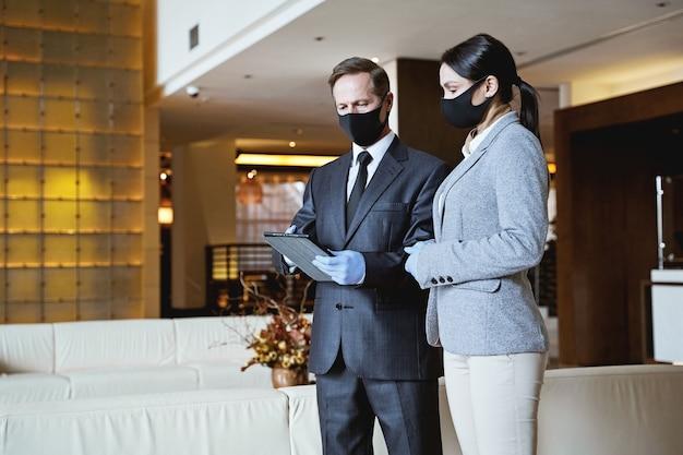 Dois colegas de trabalho em pé no saguão de um hotel e olhando para a tela do tablet. máscaras de tecido em seus rostos