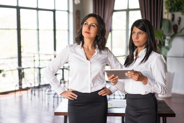 Dois colegas de trabalho fêmeas sérios que usam o pc da tabuleta no restaurante.