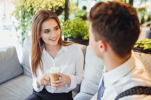 Dois colegas de trabalho se comunicam em uma pausa em um espaço inteligente. vestido com camisas brancas