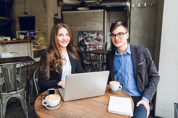 Dois colegas discutem algo perto de laptop