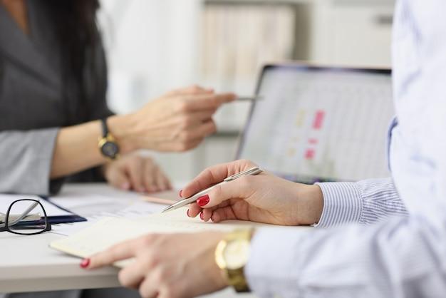 Dois colegas discutindo as métricas comerciais de negócios em tablets de pequeno e médio porte