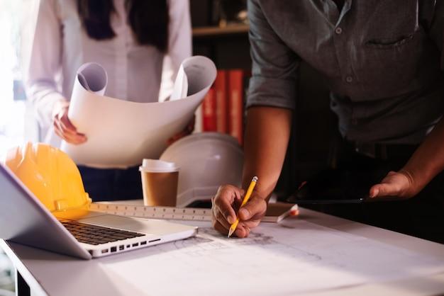 Dois colegas discutindo dados de trabalho e tablet, laptop com projeto arquitetônico no canteiro de obras na mesa no escritório