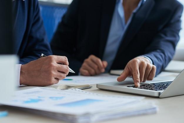 Dois colegas do sexo masculino irreconhecíveis usando laptop e gráficos de negócios deitado na mesa