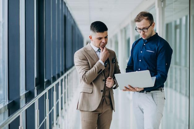 Dois colegas do sexo masculino no escritório, em pé com o laptop