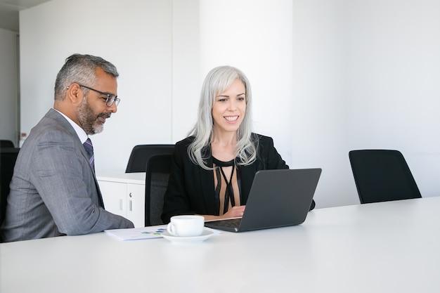 Dois colegas felizes usando laptop para videochamada, sentados à mesa com uma xícara de café, olhando para a tela e conversando. conceito de comunicação online