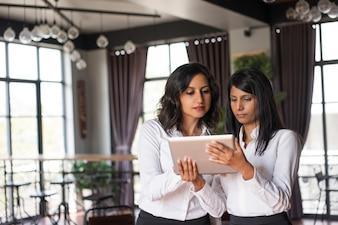 Dois colegas fêmeas focalizados que usam o tablet pc no café.