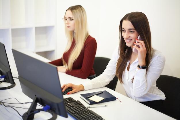 Dois colegas femininas no escritório trabalhando juntos.