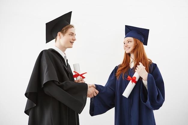 Dois colegas graduados apertam as mãos sorrindo segurando diplomas.