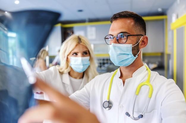 Dois colegas inteligentes e dedicados, segurando um raio-x de pulmões de pacientes e olhando para ele.