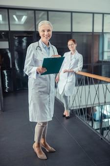 Dois colegas. médica sênior feliz com um jaleco branco em pé no corredor ao lado de seu colega sorridente Foto Premium