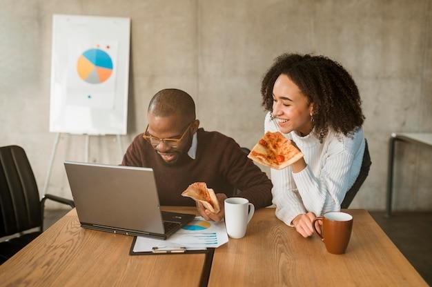 Dois colegas sorridentes comendo pizza durante um intervalo de reunião de escritório