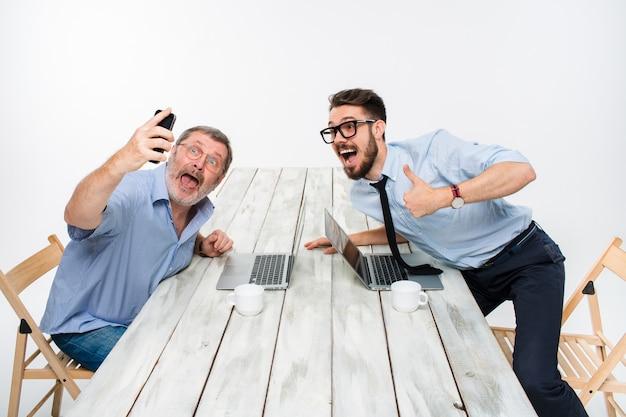 Dois colegas tirando a foto para eles auto sentado no escritório