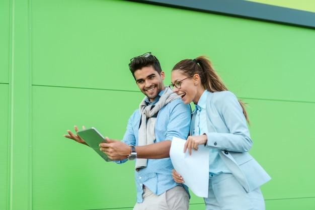 Dois colegas vestiram elegante olhando tablet enquanto caminhava na rua.
