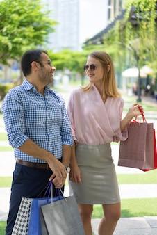 Dois compradores discutindo marcas de moda depois de visitar o shopping.