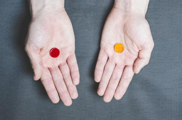 Dois comprimidos vermelhos e amarelos em mãos diferentes, escolha.