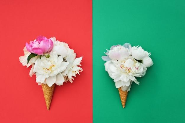 Dois cones de sorvete waffle com flores de peônia branca na mesa verde vermelha. conceito de verão. cópia de