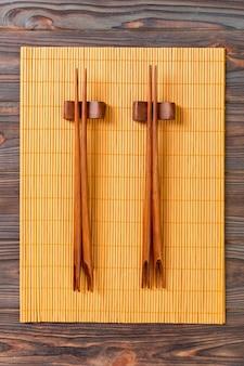 Dois conjuntos de pauzinhos de sushi em fundo de bambu de madeira, vista superior.