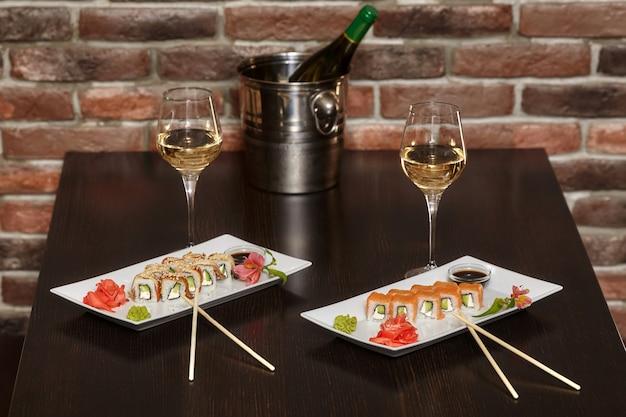 Dois conjuntos de rolos de sushi com pauzinhos e taças de vinho