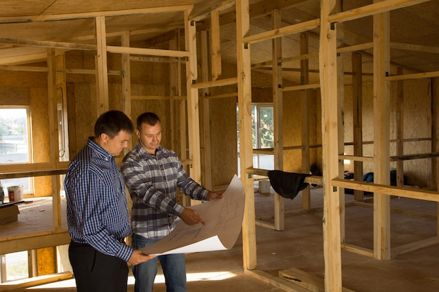 Dois construtores em pé com uma planta aberta discutindo o interior de uma casa de estrutura de madeira semi-acabada