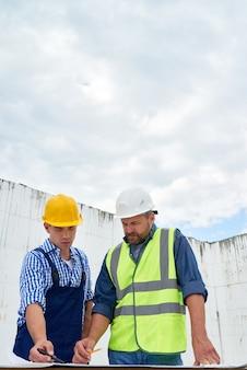 Dois construtores olhando plantas baixas no local