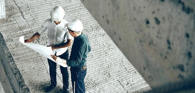 Dois construtores profissionais adultos discutindo o futuro plano de construção enquanto seguram uma grande folha de papel