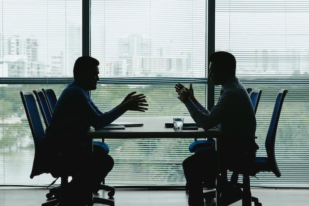 Dois contornos humanos contra a janela fechada do escritório, sentados um em frente ao outro e negociando