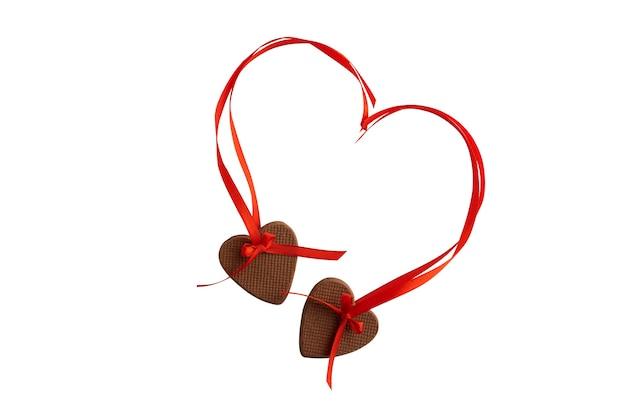 Dois cookies de coração com fitas vermelhas, isoladas no fundo branco.