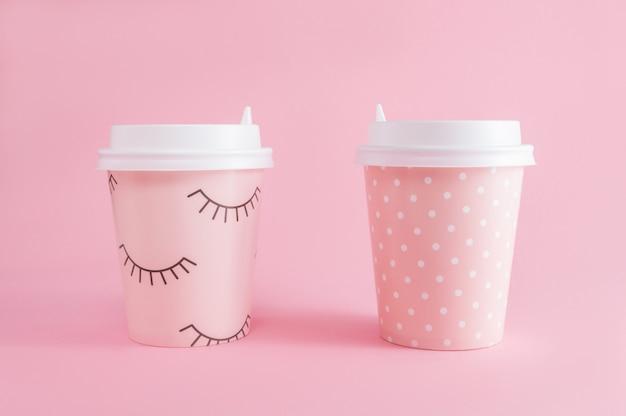 Dois copo de café take-away no fundo rosa pastel