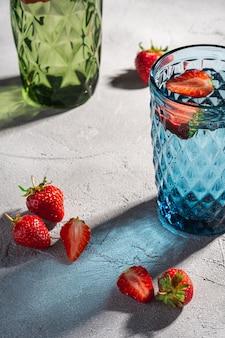 Dois copo de vidro geométrico verde e azul com frutas frescas e morango