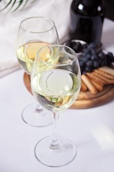 Dois copo de vinho branco e prato com queijo variado, frutas e outros petiscos para festa