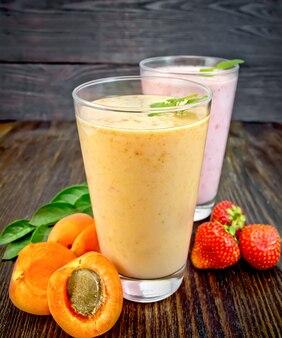 Dois copos altos de milk-shake com damascos, morangos e hortelã no fundo de uma placa de madeira
