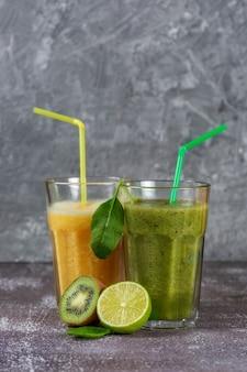 Dois copos altos de suco de laranja e um smoothie verde cercado por metades de frutas.