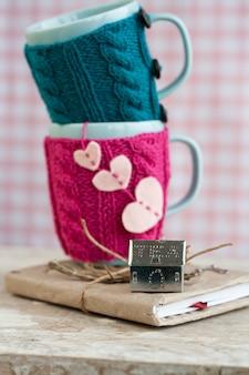 Dois copos azuis na camisola azul e rosa com corações de feltro
