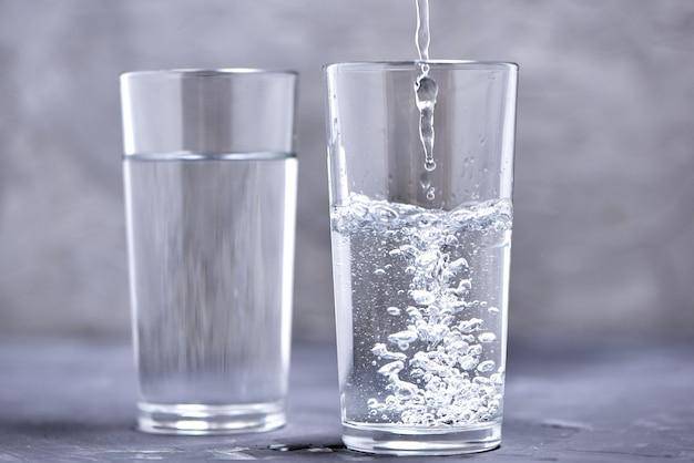 Dois copos com água em um fundo desfocado. despeje a água em um copo.