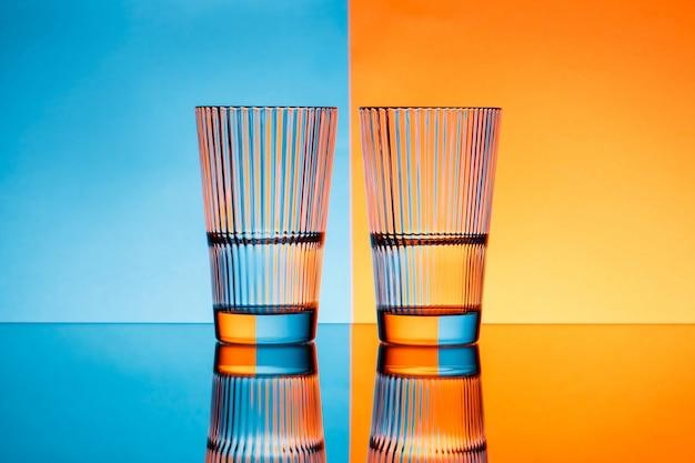 Dois copos com água sobre o fundo azul e laranja.
