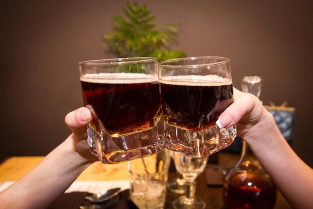 Dois copos com álcool nas mãos.
