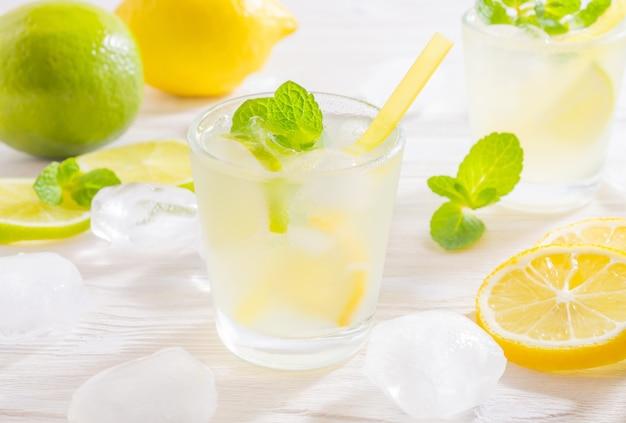 Dois copos com bebida de verão mojito com limão, limão e hortelã