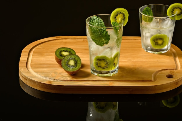 Dois copos com bebida gelada decorados com kiwi menta e gelo em uma placa de madeira isolada em um blac