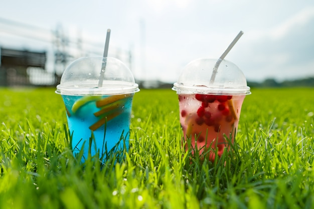Dois copos com bebida no fundo da grama verde