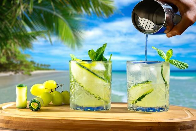 Dois copos com bebidas em uma placa de madeira ao fundo uma mão de praia segurando uma coqueteleira