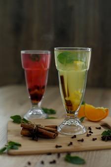 Dois copos com bebidas quentes coloridas de onde vem o vapor