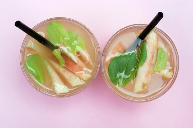 Dois copos com chá gelado caseiro com pedaços de pêssegos. bebida refrescante de verão, vista superior