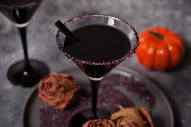 Dois copos com cocktail preto, rosas secas para festa de halloween no escuro