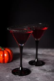Dois copos com cocktail vermelho para festa de halloween no escuro