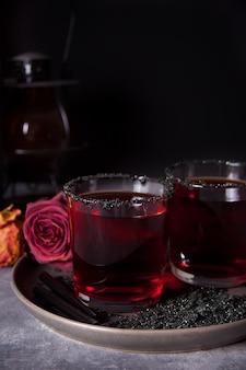 Dois copos com cocktail vermelho, rosas secas para festa de halloween no escuro