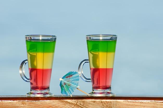 Dois copos com cocktails coloridos na parede do mar, guarda-chuva para cocktails