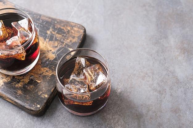 Dois copos com cola fria e cubos de gelo