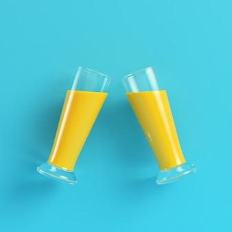 Dois copos com coquetéis amarelos em fundo azul brilhante